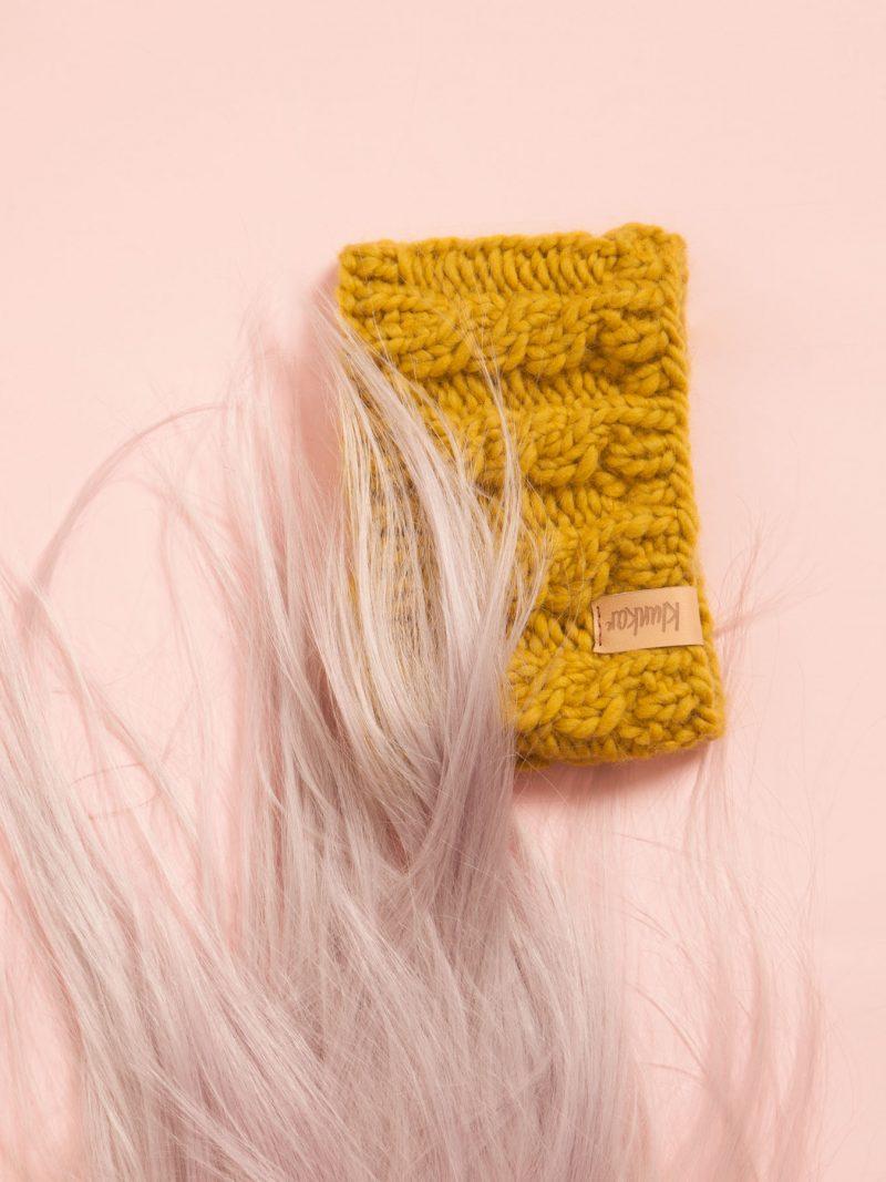Safrangelbes Stirnband auf Rosa Hintergrund mit Rosa Haaren.