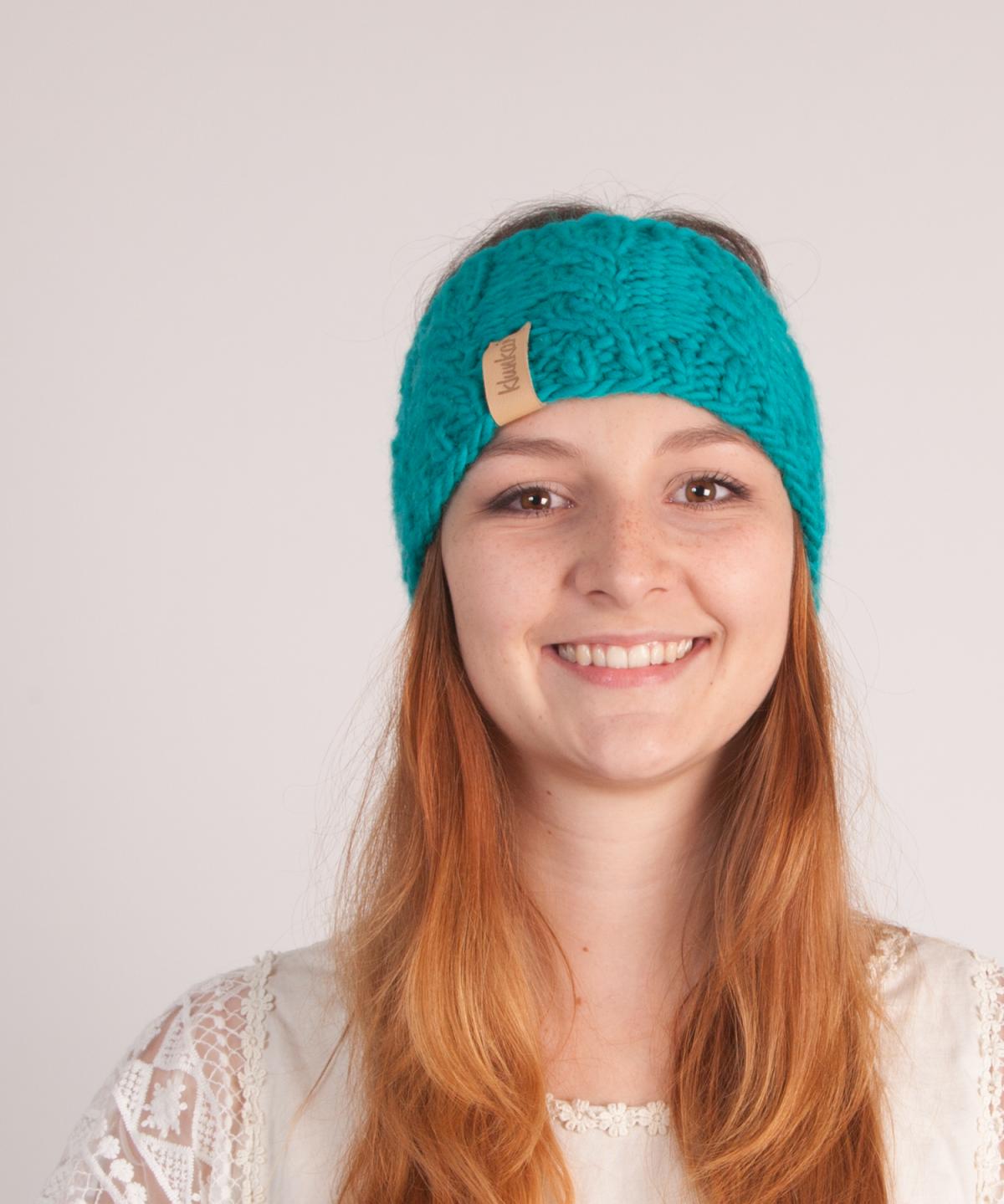 Hübsche, lächelnde Frau trägt türkisblaues Stirnband.