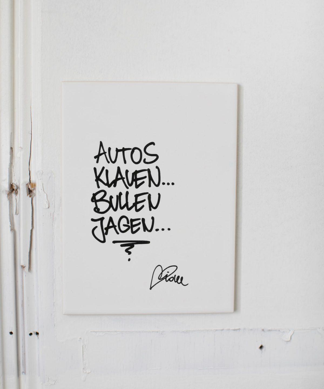 """Streetartis idee schreibt """"Autos klauen, bullen jagen"""". Weiße Wandkachel für deine Wand zuhause. Foto von Nina Bröll."""