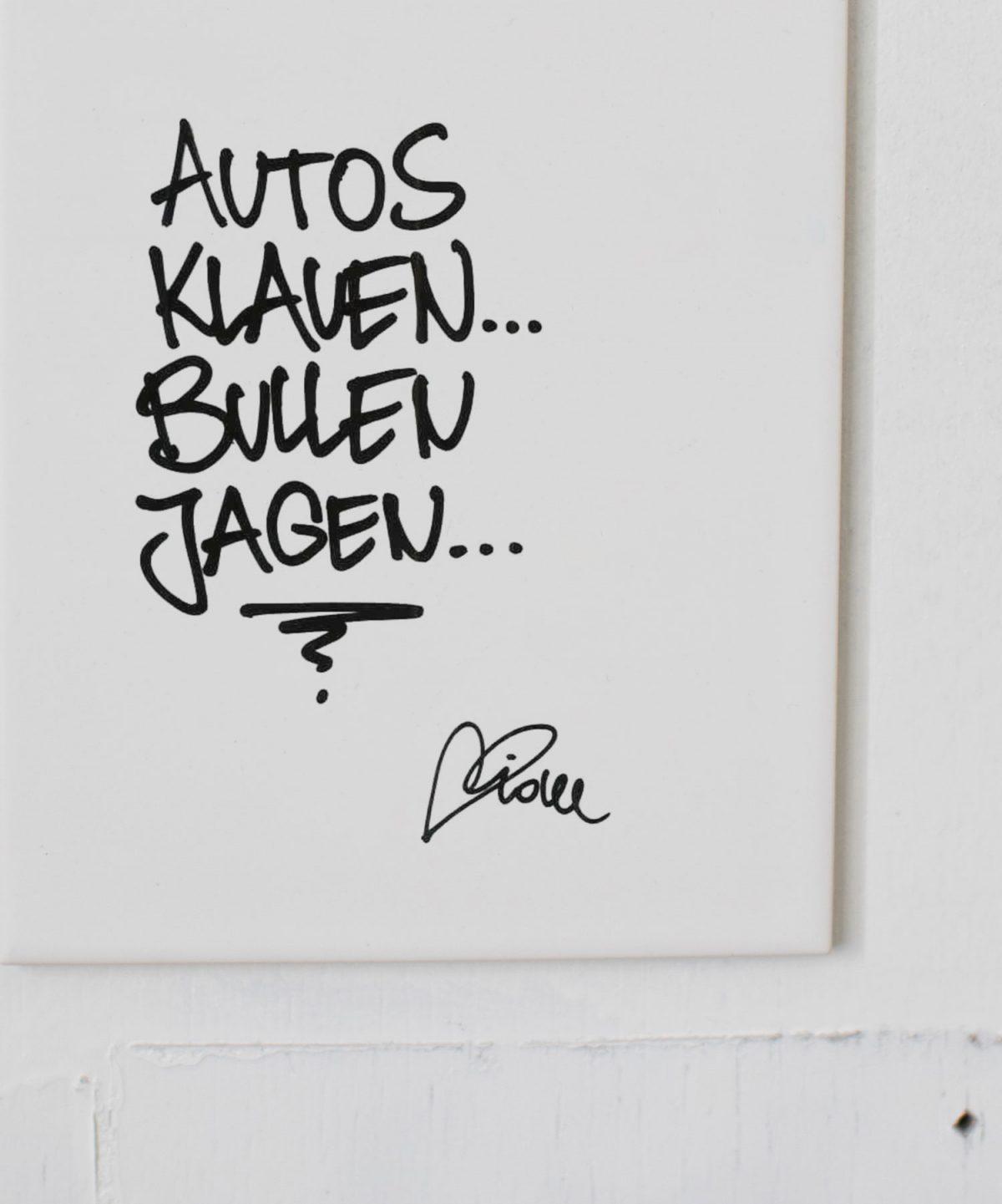 """Weiße Wandkachel mit Handlettering """"Autos klauen, Bullen jagen."""" von Streetartist idee. Foto von Nina Bröll."""