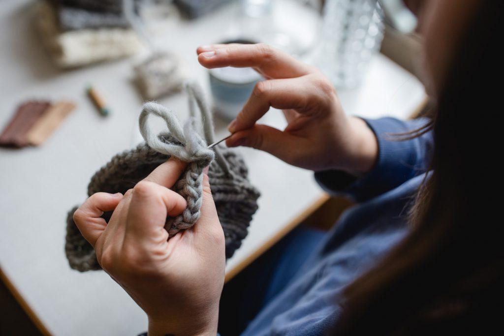 Feinste Handarbeit. Mit einer großen Teppichnadel vernäht Simone Angerer die Merino Wolle. Foto von Nina Bröll.