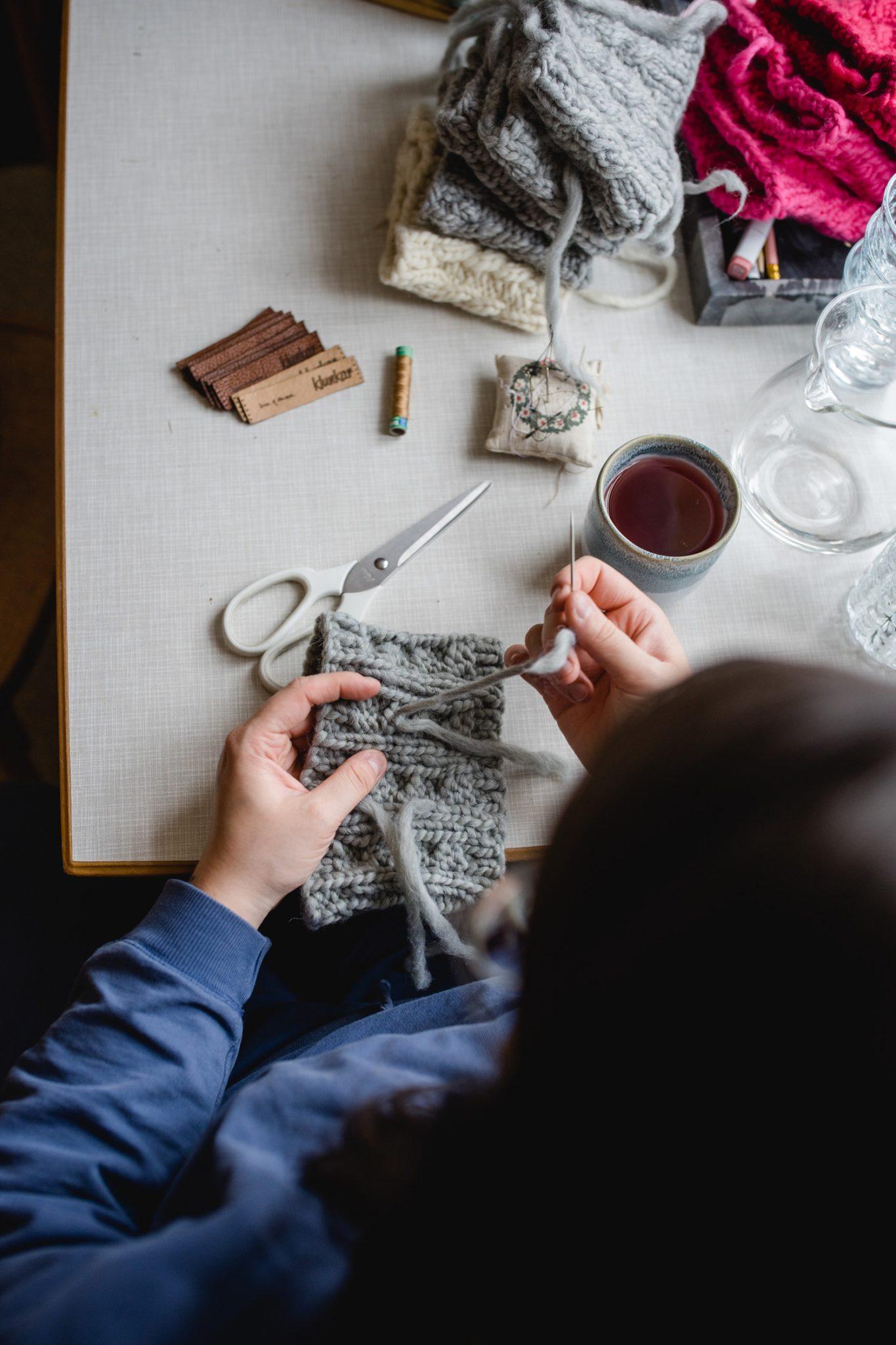 Am Arbeitstisch bei House of Klunkar. Simone Angerer vernäht Wollenden der Stirnbänder. Foto von Nina Bröll.