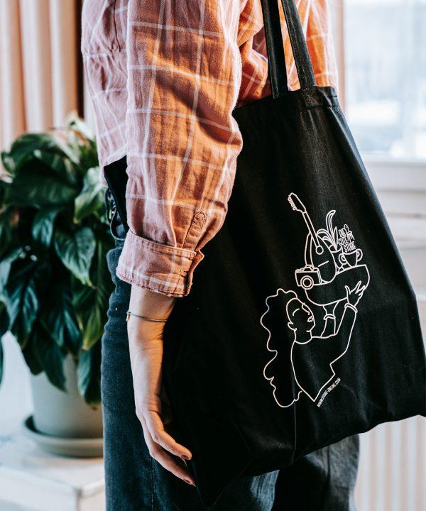 Schwarze Stofftasche mit Illustration von der Guten Stube Andelsbuch. Foto von Pia Pia Pia Berchtold.